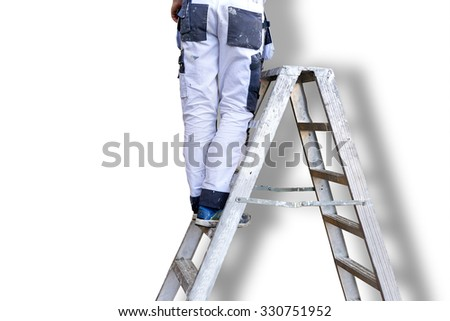 Legs of man in white stained overalls on metal stepladder, white wall with shadow in background - stock photo