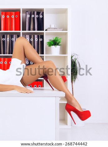 legs of sexy businesswoman lying on table at office - stock photo
