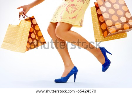 Legs of shopper in high-heeled shoes with colorful paper bags in move - stock photo