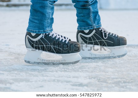 Legs of skater on winter ice rink