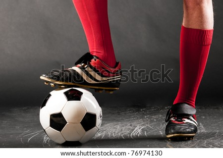 legs of soccer player with ball on dark background - stock photo