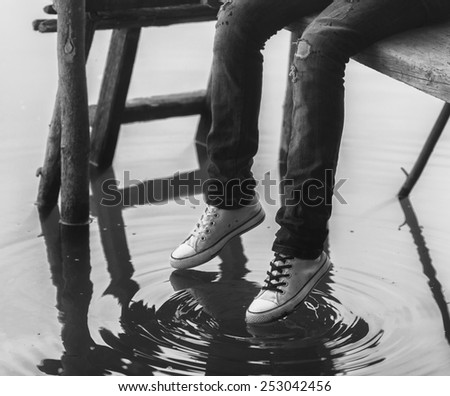 Legs of teenager sitting on the wooden dock and touching water. - stock photo