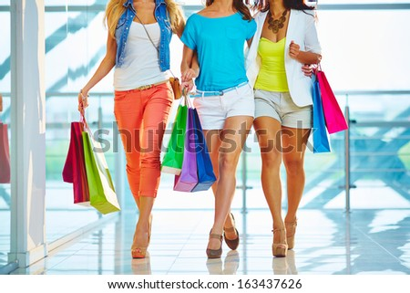 Legs of three glamorous girlfriends with paperbags walking down trade center - stock photo