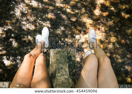 Legs of two girls seated on the river - stock photo
