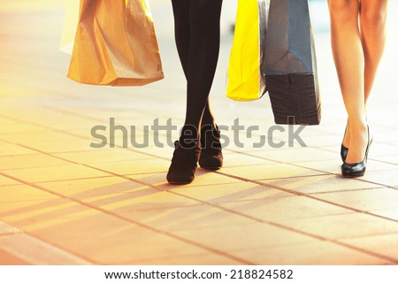 Legs of two glamorous girlfriends with paperbags. Big Sale Shopping - stock photo