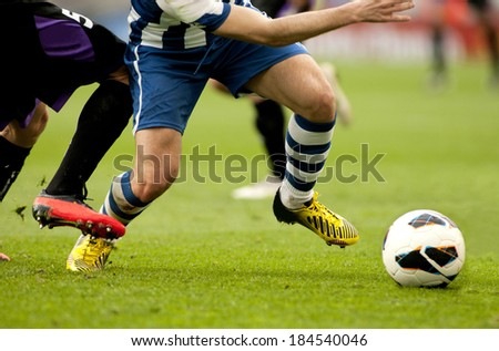 Legs of two soccer players vie on a match - stock photo