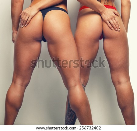 Legs of two woman in swim wear. - stock photo