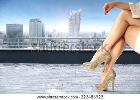 legs of woman and blue sky with city  - stock photo
