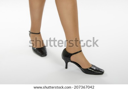 Legs of woman dancer in crocodile leather shoes on white background