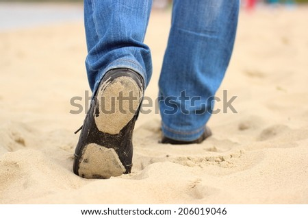 Legs of woman on the beach, woman walking in comfortable black shoes outdoor on the beach - stock photo