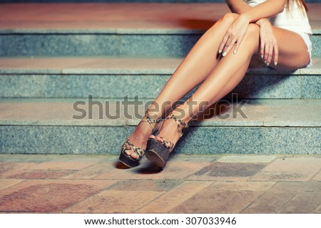 Legs of woman sitting on stairs. Toned image instagram style color - stock photo