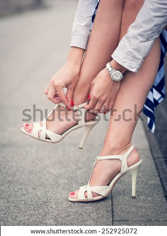 Legs of woman with high heels white sandals outdoor - stock photo