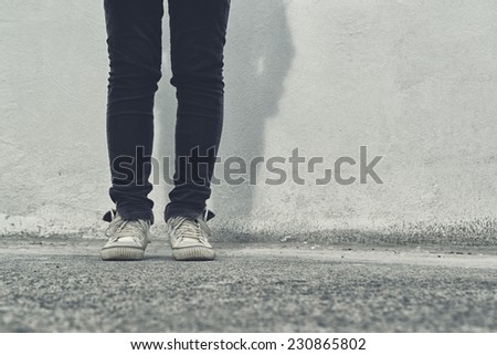 Legs of Young adult woman in black pants and white sneakers standing on the street.
