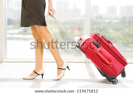 Legs of young businesswoman with baggage in airport - stock photo