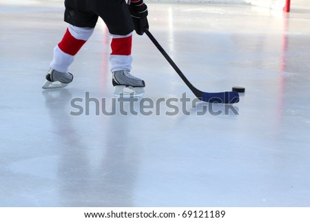 Legs of young child playing outdoor pond hockey - stock photo