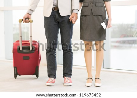Legs of young couple with baggage in airport - stock photo