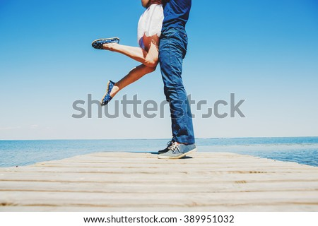 legs of young hugging couple on the turquoise beach - stock photo