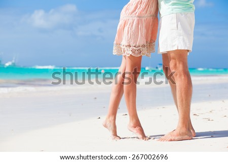 legs of young hugging couple on tropical turquoise beach - stock photo