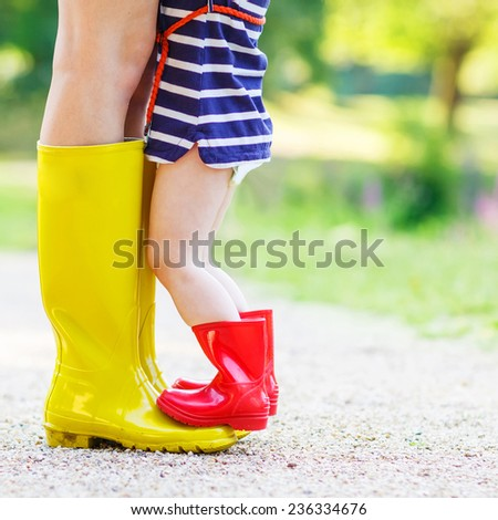 Legs of young woman and her little girl daughter in rain boots. - stock photo
