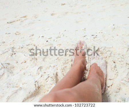 Legs of young woman lying in the sand on the beach. Close-up - stock photo