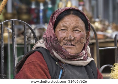 LEH, INDIA - JUNE 21, 2015: Unidentified beggar woman on the street in Leh, Ladakh. Poverty is a major issue in India