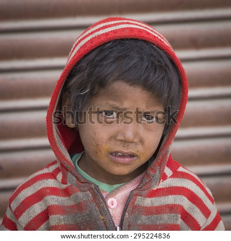 LEH, INDIA - JUNE 29, 2015: Unidentified poor Indian beggar boy on street in Ladakh. Children of the early ages are often brought to the begging profession. - stock photo