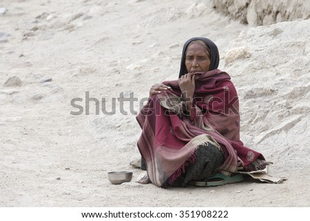 LEH, INDIA - JUNE 24, 2015: Unknown poor woman begs for money from a passerby on the street in Leh, Ladakh. Poverty is a major issue in India - stock photo