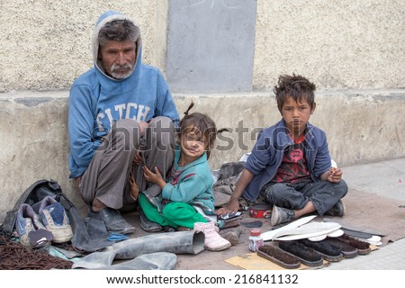 LEH, INDIA - SEPTEMBER 08 2014: An unidentified beggar family begs for money from a passerby in Leh. Poverty is a major issue in India - stock photo