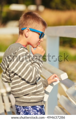 Leisure and free time concept. Portrait of little boy spending time outside on fresh air. Male kid outdoor on holidays vacation.