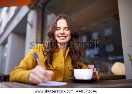 leisure and people concept - happy young woman or teenage girl with cup drinking cocoa and writing to notebook at city street cafe terrace