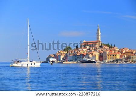 Leisure boat sailing in the harbor of old Venetian town near the Adriatic sea, Rovinj, Croatia - stock photo