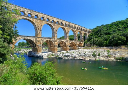 Leisure boats on a river passing under the Pont du Gard near Nimes, France - stock photo