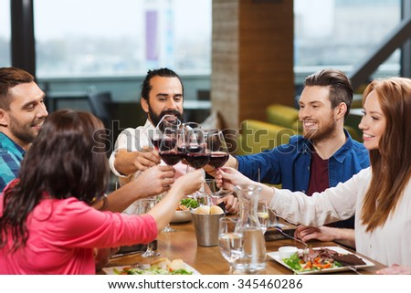 leisure, celebration, food and drinks, people and holidays concept - smiling friends having dinner and drinking red wine at restaurant - stock photo