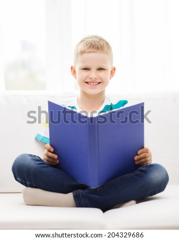 leisure, childhood, education and home concept - smiling little boy reading book and sitting on couch at home - stock photo