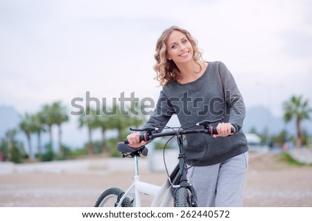 Leisure day at the beach. Attractive young blond woman with beautiful curl long hair walking with a bicycle against mountains background. - stock photo