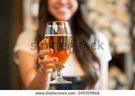 leisure, drinks, degustation, people and holidays concept - close up of smiling woman hand holding glass of draft lager beer - stock photo