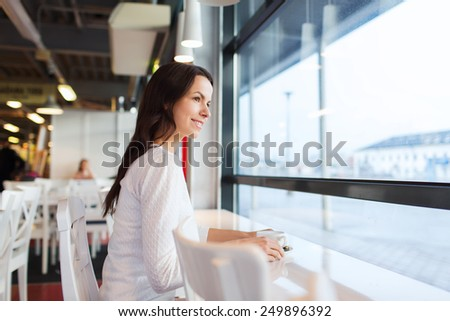 leisure, drinks, people and lifestyle concept - smiling young woman drinking coffee at cafe - stock photo