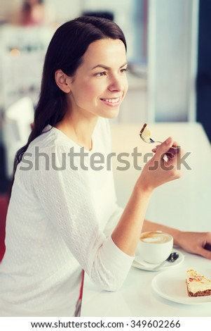 leisure, drinks, people and lifestyle concept - smiling young woman eating cake and drinking coffee at cafe - stock photo