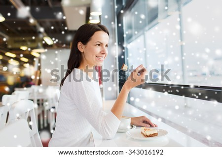 leisure, drinks, people, holidays and lifestyle concept - smiling young woman eating cake and drinking coffee at cafe over snow effect - stock photo