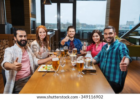 leisure, eating, food and drinks, people and holidays concept - smiling friends having dinner and drinking beer and showing thumbs up at restaurant or pub - stock photo