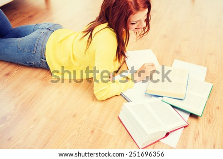 leisure, education and home concept - smiling teenage girl reading books on floor - stock photo