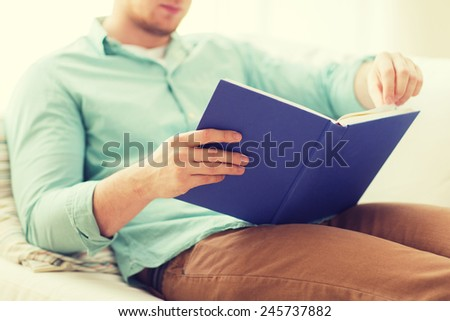 leisure, education, literature and home concept - close up of man and sitting or lying on couch and reading book at home - stock photo