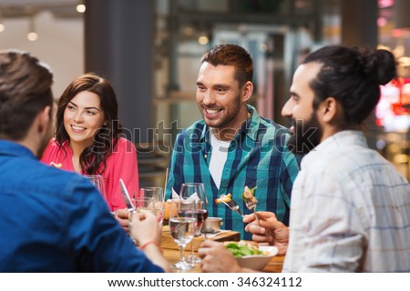 leisure, food and drinks, people and holidays concept - happy friends having dinner at restaurant - stock photo