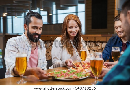 leisure, food and drinks, people and holidays concept - smiling friends eating pizza and drinking beer at restaurant or pub - stock photo