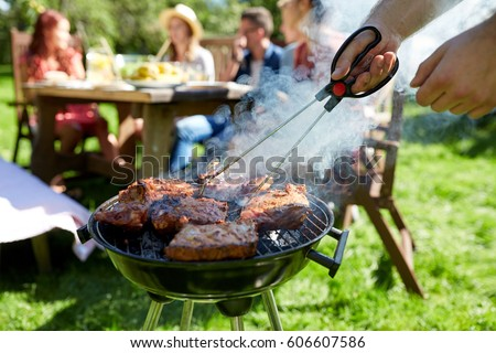 leisure, food, people and holidays concept - man cooking meat on barbecue grill for his friends at summer outdoor party