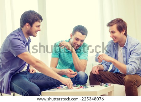 leisure, games and lifestyle concept - happy three male friends playing poker at home - stock photo