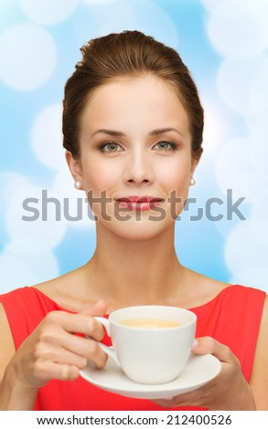 leisure, happiness and drink concept - smiling woman in red dress with cup of coffee over blue lights background - stock photo