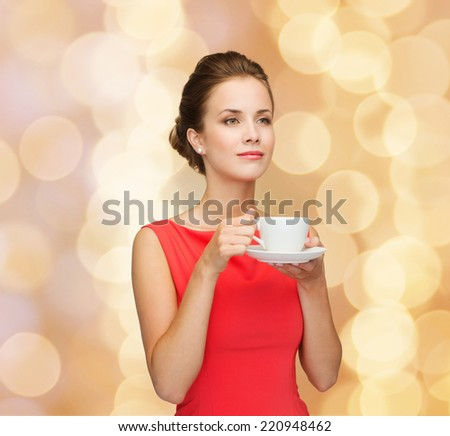 leisure, happiness and drink concept - smiling woman in red dress with cup of coffee over golden lights background - stock photo