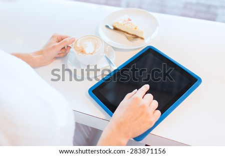 leisure, people, technology and lifestyle concept - close up of young woman hands with tablet pc computer drinking coffee and eating cake at cafe - stock photo