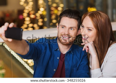 leisure, technology, date, people and holidays concept - happy couple taking selfie by smartphone at restaurant